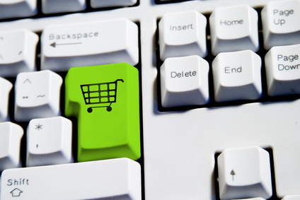 Computer Keyboard from a desktop computer with the enter key highlighted in green with a large shopping cart on it